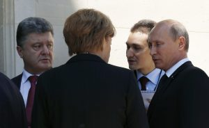Ukraine president-elect Petro Poroshenko (L), German Chancellor Angela Merkel (C) and Russian President Vladimir Putin (R) talk after a group photo during the 70th anniversary of the D-Day landings in Benouville, France June 6, 2014. Putin spoke with Poroshenko on Friday on the sidelines of D-Day commemorations in France as they met with Merkel, a Reuters reporter said. REUTERS/Kevin Lamarque  (FRANCE - Tags: POLITICS ANNIVERSARY CONFLICT)