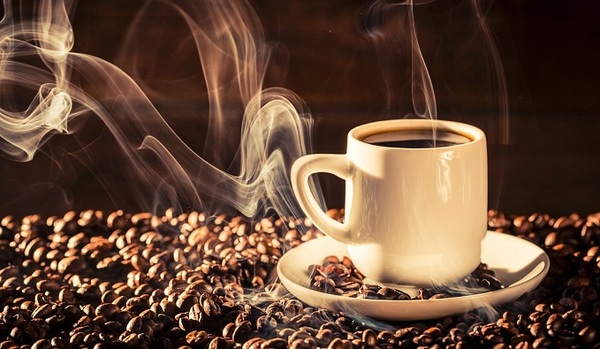 A cup of hot coffee on coffee beans