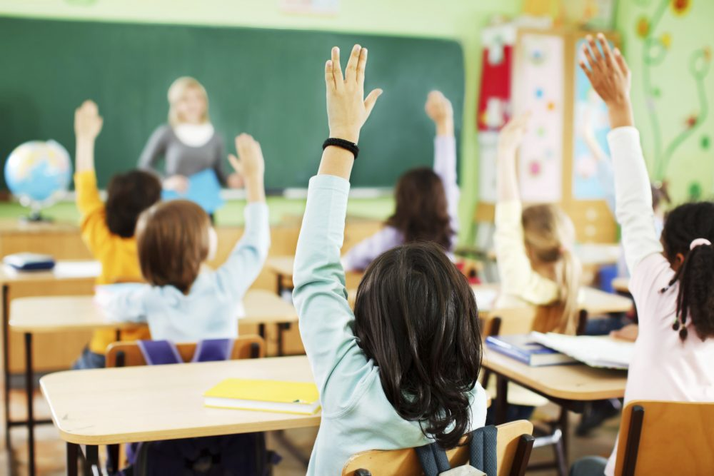 Children are raised hands in classroom.